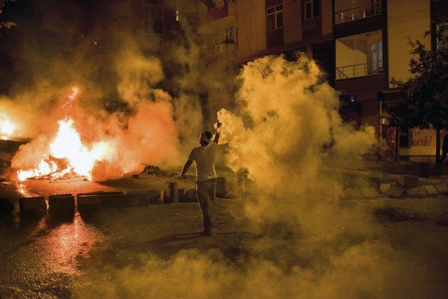 A protestor returns tear gas at police in Gazi Mahellesi on Saturday night. Photo © Justin Wilkes, click for more photos